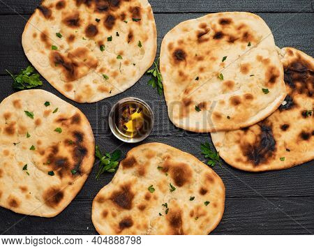 Fresh Naan Bread On Dark Wooden Background With Copy Space. Several Perfect Naan Flatbreads Top View