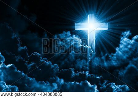 Christian Religion Concept Shining Cross On Dramatic Cloudy Night Sky Background. Dark Sky With Cros
