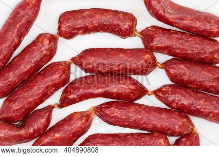Small Thin Dry Cured Sausages In Natural Casing On A White Surface, Fragment Top View, Background