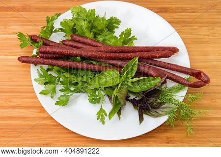Long Thin Dry Cured Sausages In Natural Casing On A Dish Among The Different Fresh Greens On A Woode