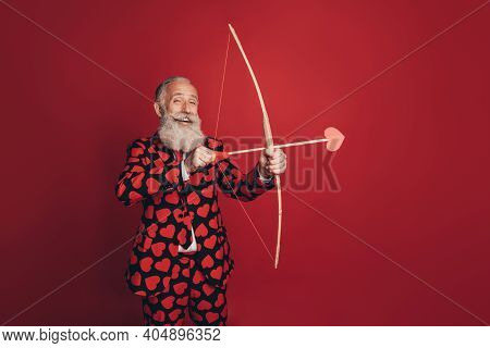 Photo Of Positive Retired Cherub Man Hold Bow Arrow Prepare Shoot Wear Heart Print Tux Isolated Red