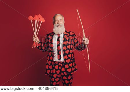 Photo Of Cheerful Retired Cherub Archer Hold Bow Arrow Look Camera Wear Heart Print Tux Isolated Red