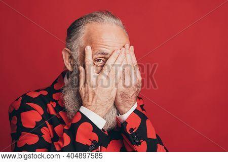 Photo Of Funny Shy Bearded Man Palms Hide Face Peeking Eye Wear Heart Print Suit Isolated Red Backgr