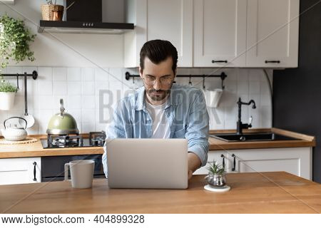 Concentrated Millennial Male Engaged In Telework From Home Using Laptop