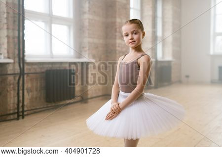 Portrait of little ballet dancer in tutu dress looking at camera standing in dance school