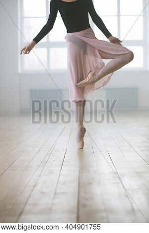 Close-up of woman in tutu dress and in pointe shoes standing on one leg and practicing ballet in studio