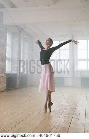 Young graceful woman in tutu dress dancing ballet alone in dance school
