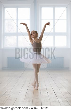 Little girl in tutu dress and pointe shoes raising her hands up and dancing ballet in studio