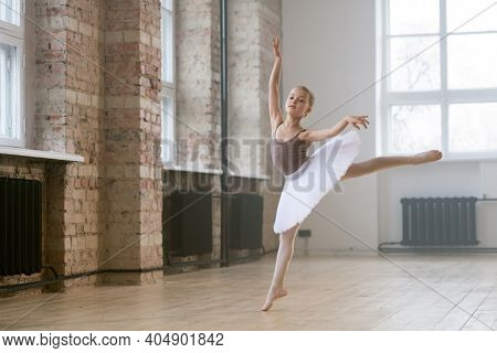Adorable child dancing classical ballet in a white studio