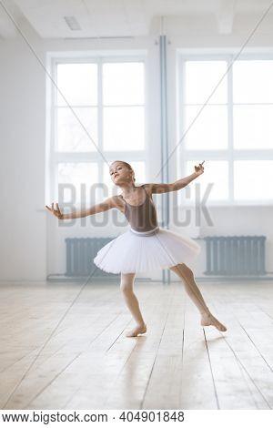 Little ballerina in tutu dress performing ballet dance alone in dance hall