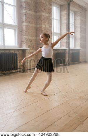 Little ballerina learning to dance during ballet training at studio