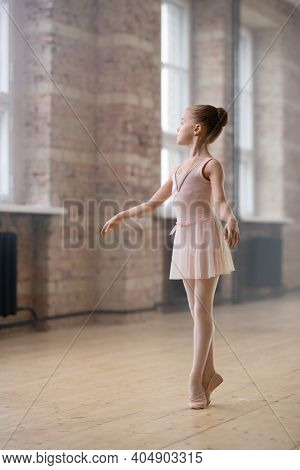 Beautiful little ballerina standing on her toes and training in dance hall