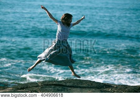 An dancer woman is engaged in choreography on the rocky coast of Atlantic ocean in Portugal.