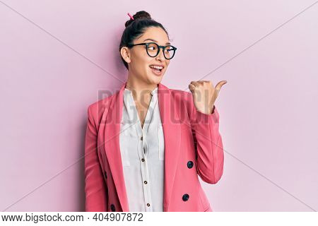 Beautiful middle eastern woman wearing business jacket and glasses smiling with happy face looking and pointing to the side with thumb up.