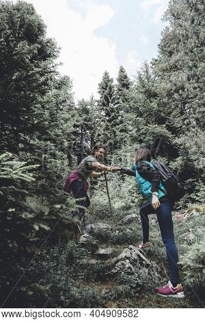 Beautiful Young Couple Having Fun Mountaineering Through An Evergreen Forest, Relaxing In Nature On