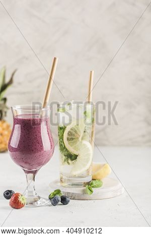 Two Glasses Of Drinks, A Smoothie Made From Fresh Berries And A Mojito With Lemon And Mint On A Ligh