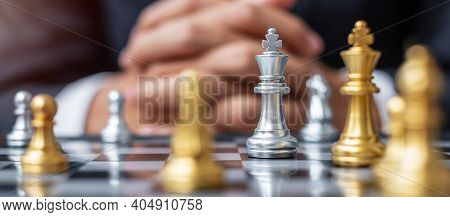 Silver Chess King Figure Against Goal Chessboard Opponent With Businessman Manager Background. Strat