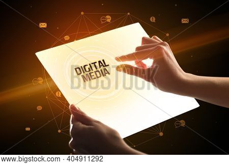 Holding futuristic tablet with DIGITAL MEDIA inscription, social media concept