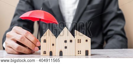 Businessman Hand Holding Red Umbrella Cover Wooden Home Model On Table Office. Property Insurance An