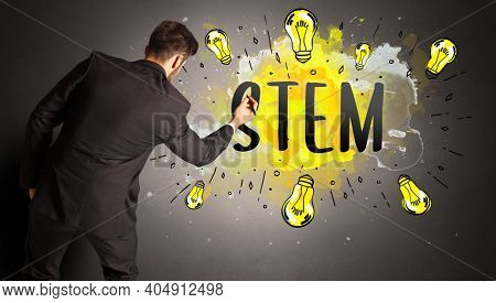 businessman drawing colorful light bulb with STEM abbreviation, new technology idea concept