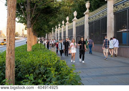 August 8, 2020, Moscow, A Crowd Moves Along The Sidewalk Along The High Red Fence With Gilding, Park