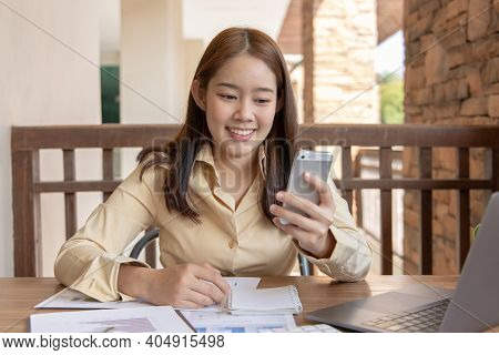 Asian female employees are analyzing market data via smartphones and have laptops to calculate the c
