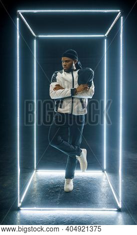 Rapper posing in illuminated cube, dark background