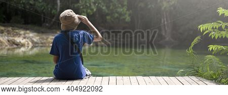Young Boy Sitting On Wooden Bridge And Enjoying Looking Forest Views On Vacation Travel