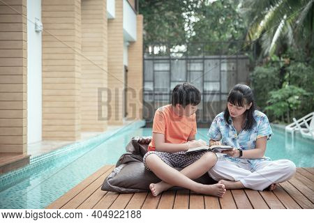 Portrait Young Woman Reading A Book On The Bed Pillow , Lifestyle Women Read Book In Park