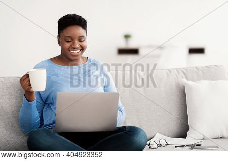 Smiling African American Woman Sitting On The Couch, Holding Coffee Mug And Working On Laptop. Lady