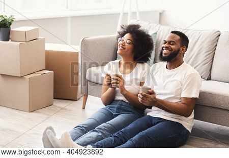 Happy Black Couple Celebrating Moving To New Apartment Sitting Among Unpacked Boxes And Having Coffe