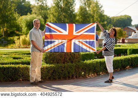 Mature Man And Woman Holding British Flag. Patriotic Family Outdoors. Huge Flag Of The United Kingdo
