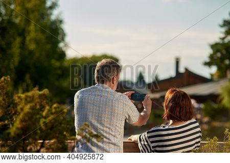 Back View Mature Man Taking A Photo On His Smartphone. Adult Senior Couple Enjoying The Nature Sitti