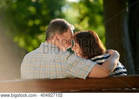 Happy Mature Smiling Couple. Back View Man And Woman Sitting On The Bench Outdoors.