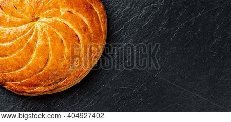 Epiphany cake or galette des rois in French on black slate background, panoramic crop with copy space