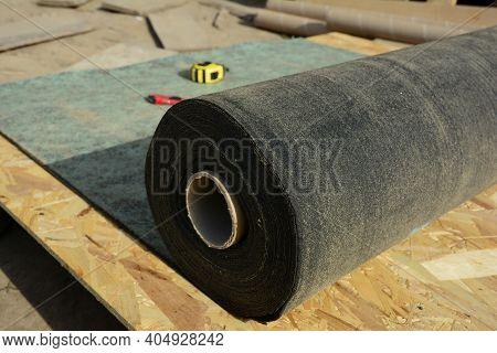 Unrolling Waterproofing, Water-resistant Felt, Bituminous Roofing Underlayment On The Roof Sheathing