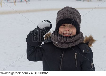 A Preschool Boy In Winter Clothes Aims A Snowball In The Winter. A Child Can Play Snowballs In Winte