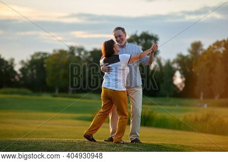 Man And Woman Danicng Tango Outdoors. Green Field Background.