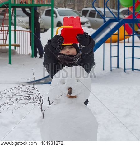 A Preschool Boy Made A Snowman Out Of Snow In Winter And Puts A Red Bucket On The Snowman's Head