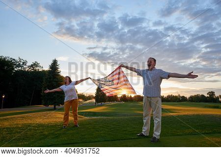 Man And Woman Holding Usa Flag Outdoors. Patriotic Couple Holding Flag Of The United States.