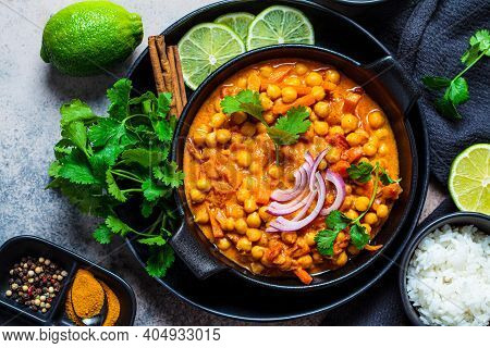 Vegan Chickpea Curry With Rice And Cilantro In A Black Bowl, Dark Background. Indian Cuisine Concept