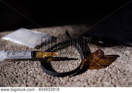 Heroin In Syringe And Powder Heroin On Spoon And Plastic Bag Pack With Yellow Rubber Band On Dark Ce