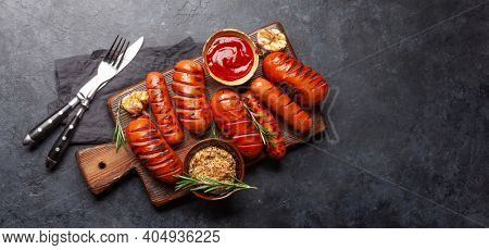 Hot grilled sausages on wooden board with ketchup and mustard. Top view flat lay with copy space