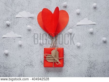 Flat lay Happy Valentine's Day photography with gift box and paper origami heart in air balloon shape. Cute romantic greeting card.