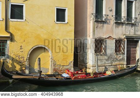 Venice Canal And Gondola. Tourists From All The World Enjoy The Historical City Of Venezia In Italy,