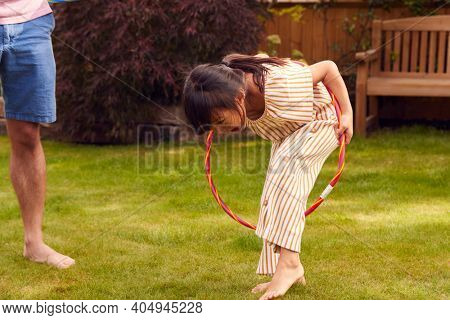 Asian Father And Daughter Having Fun Playing With Hula Hoop In Garden At Home