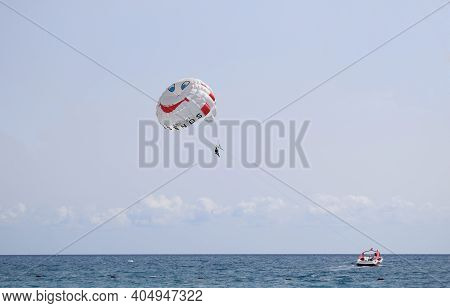 Parasailing Water Amusement - Flying On A Parachute Behind A Boat On A Summer Holiday By The Sea In