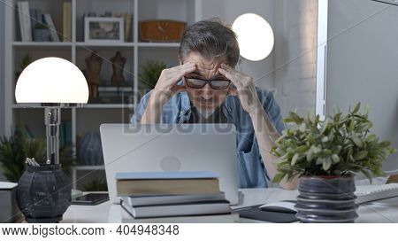 Older man working online with laptop computer at home sitting at desk. Home office, surfing internet, study room.