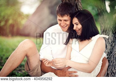 A Pregnant Girl And A Guy Sit Under A Tree In The Park And Look At The Ultrasound Photo Of The Unbor
