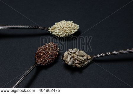 Various Seeds On A Black Background. Three Spoons With Flax Seeds, Sesame Seeds And Sunflower Seeds.